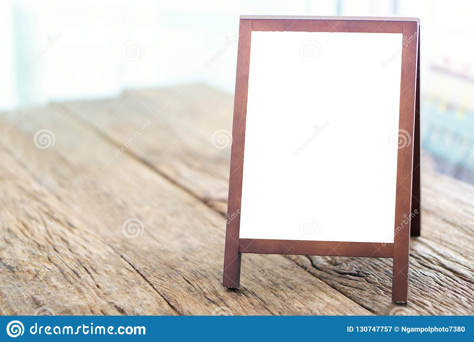 Mock up blank advertising whiteboard with easel standing on wood