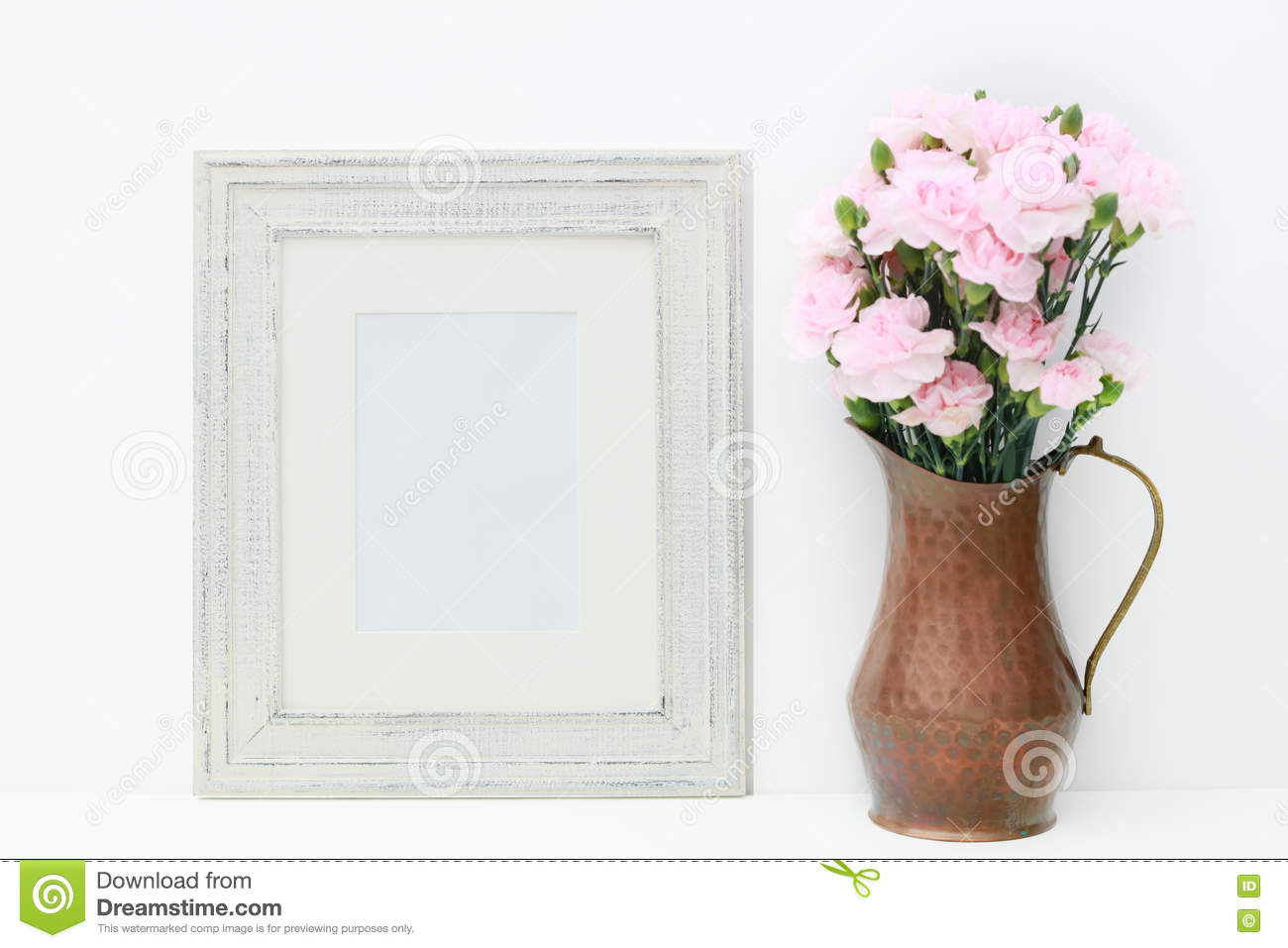 A mock up of a empty white frame and flowers.