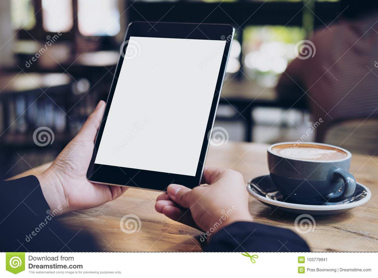 Business woman`s hands holding black tablet with white blank screen and coffee cup on wooden table in cafe