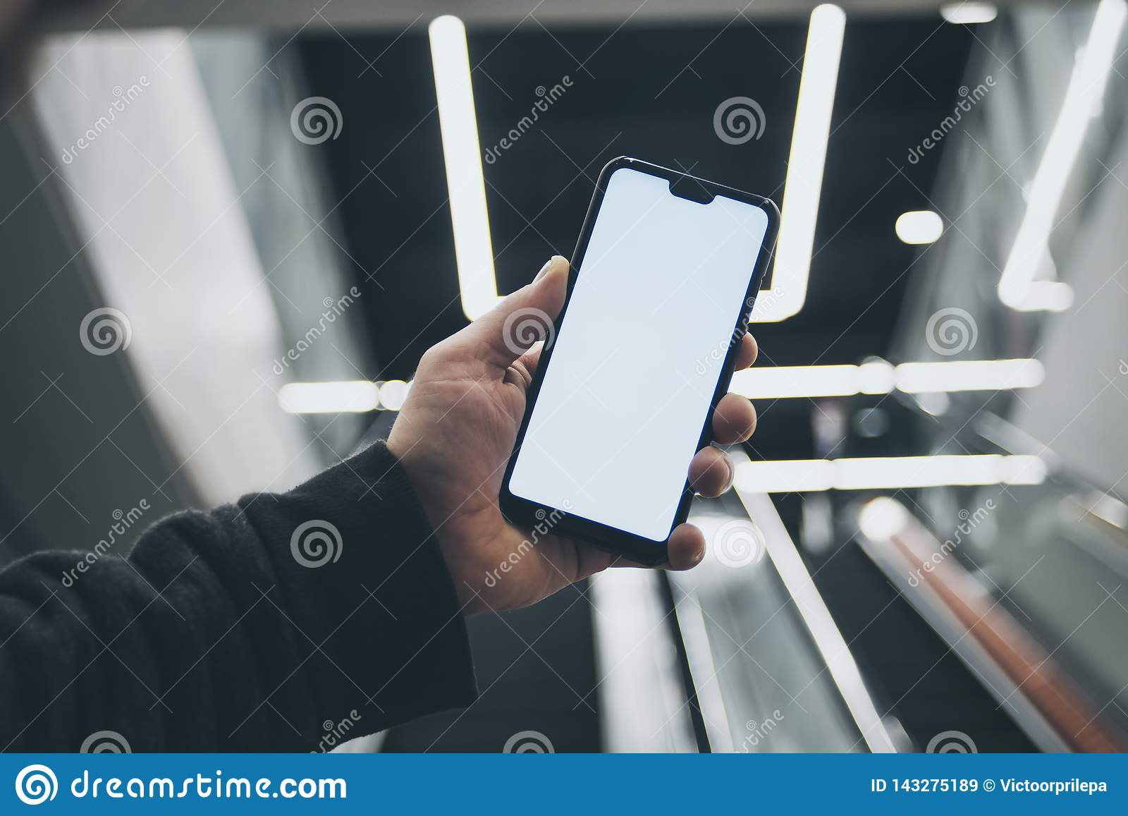 Mock up of a smartphone in hand, on the background of an escalator in a shopping center and luminous lamps.