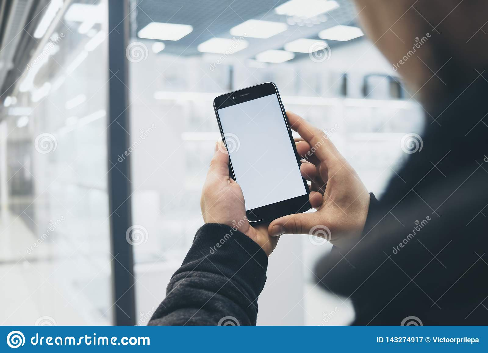 Mock up of a smartphone in hand, on the background of a shopping center.