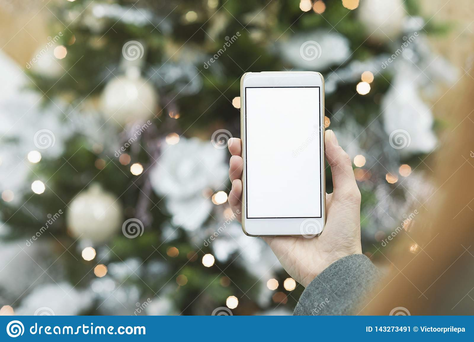 Mock up of the smartphone in the hand of the girl on the background of the Christmas tree with a festive decoration.