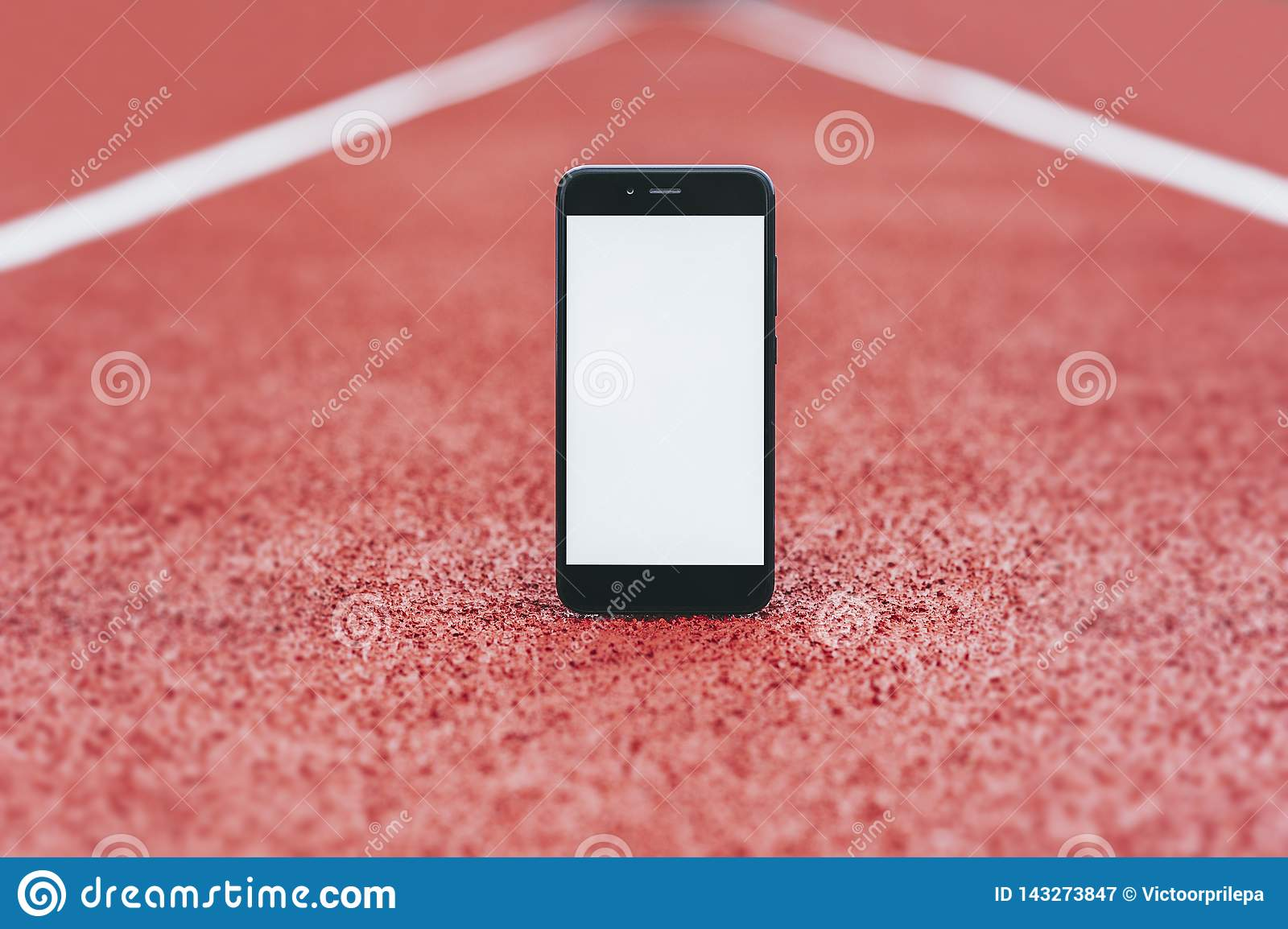 Mock Up smartphone at the stadium for running. Concept on the topic of sport.