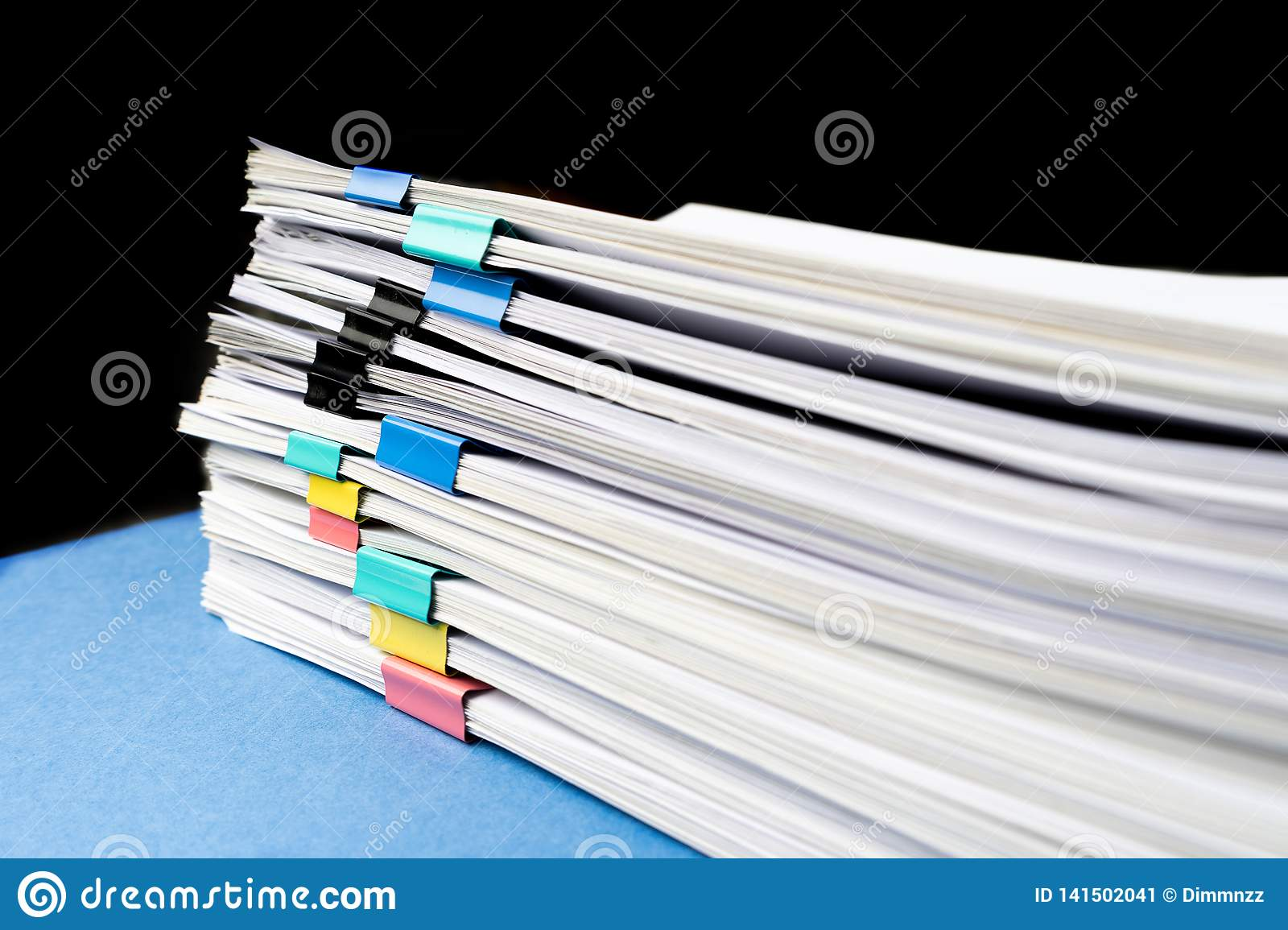 Mock up, stack of papers documents in archives files with paper clips on desk at offices, business concept. Copy space