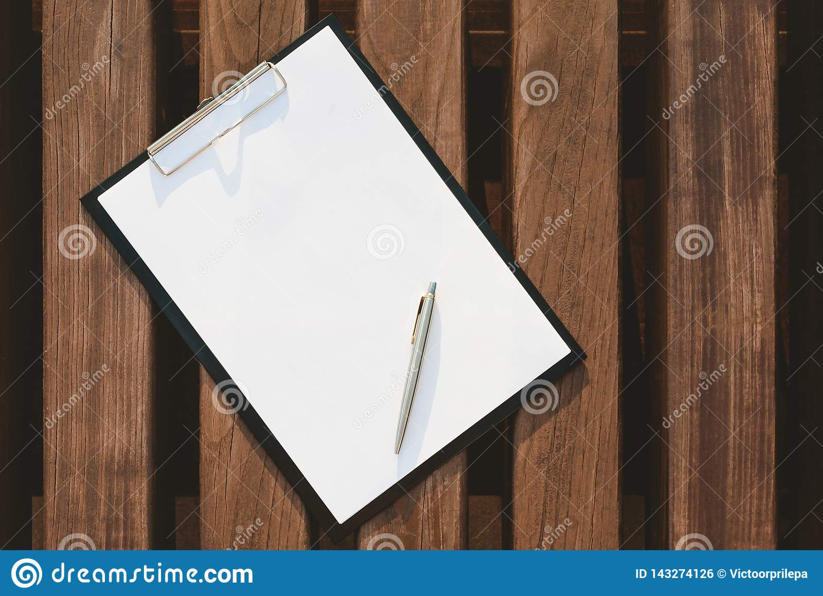 Mock Up of the tablet for the paper on the background of wooden wall.