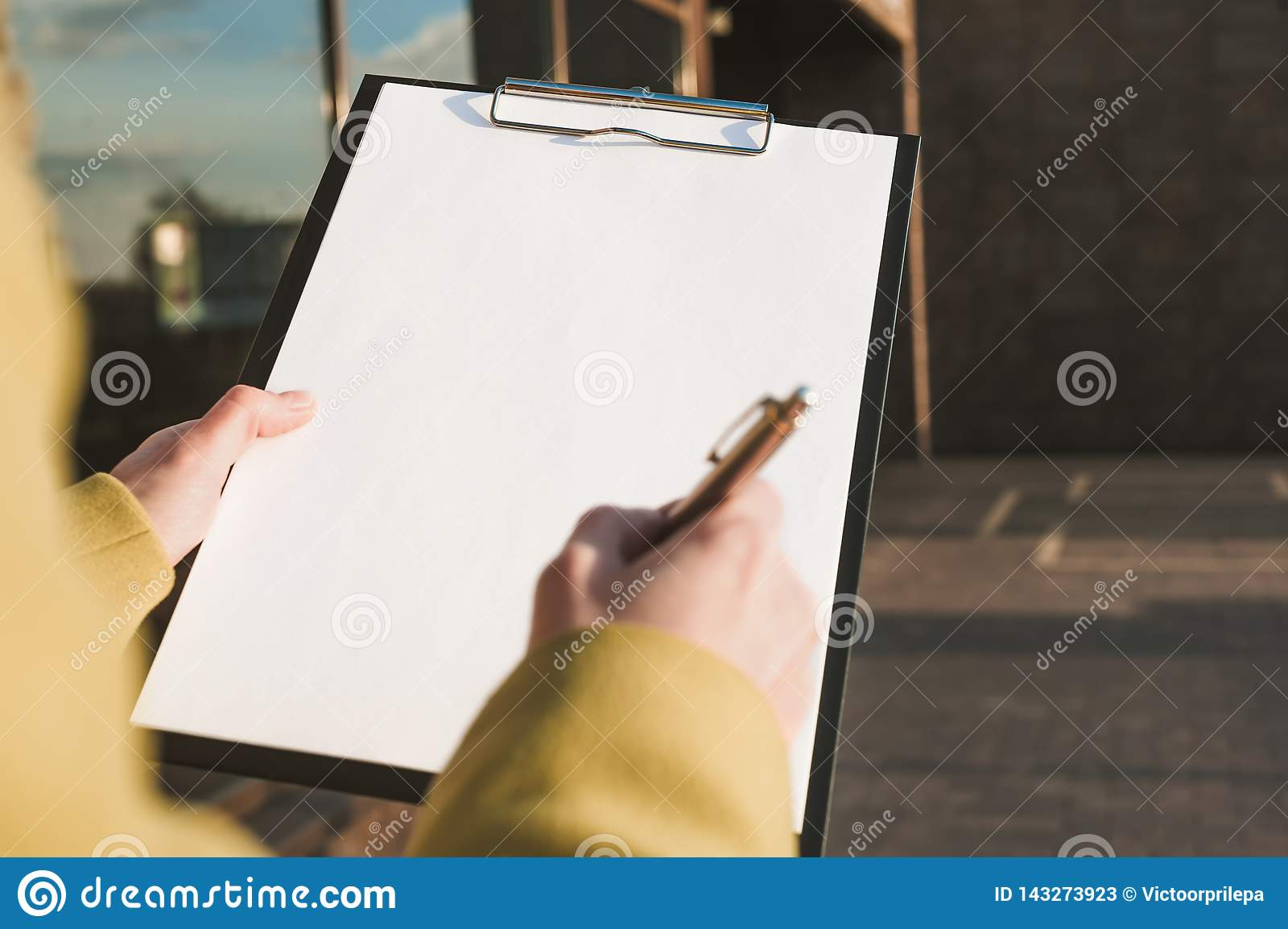 Mock Up of the tablet for the paper in the hands of the girl against the background of the glass center
