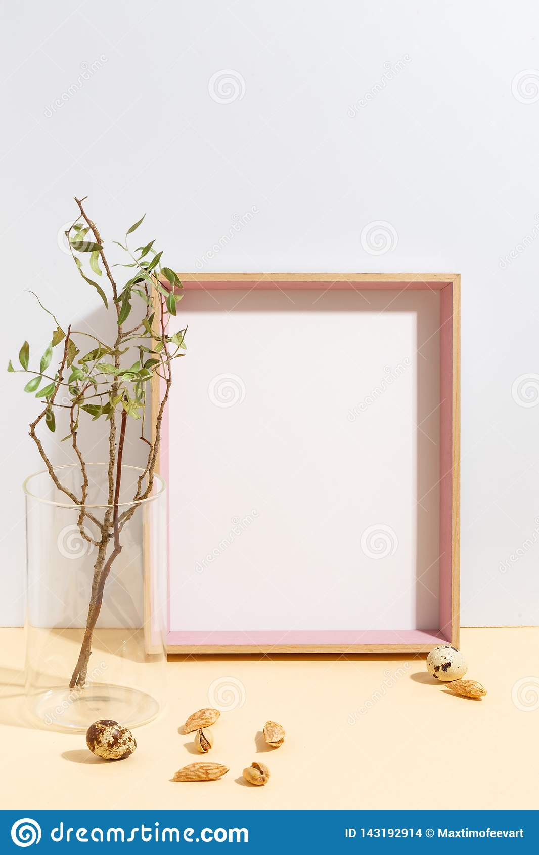 Mock up white frame and branch with green leaves in blue vase on book shelf or desk. Minimalistic concept