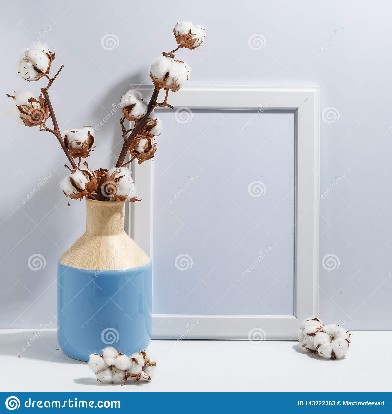 Mock up white frame and dry cotton twigs in blue vase on book shelf or desk. Minimalistic concept