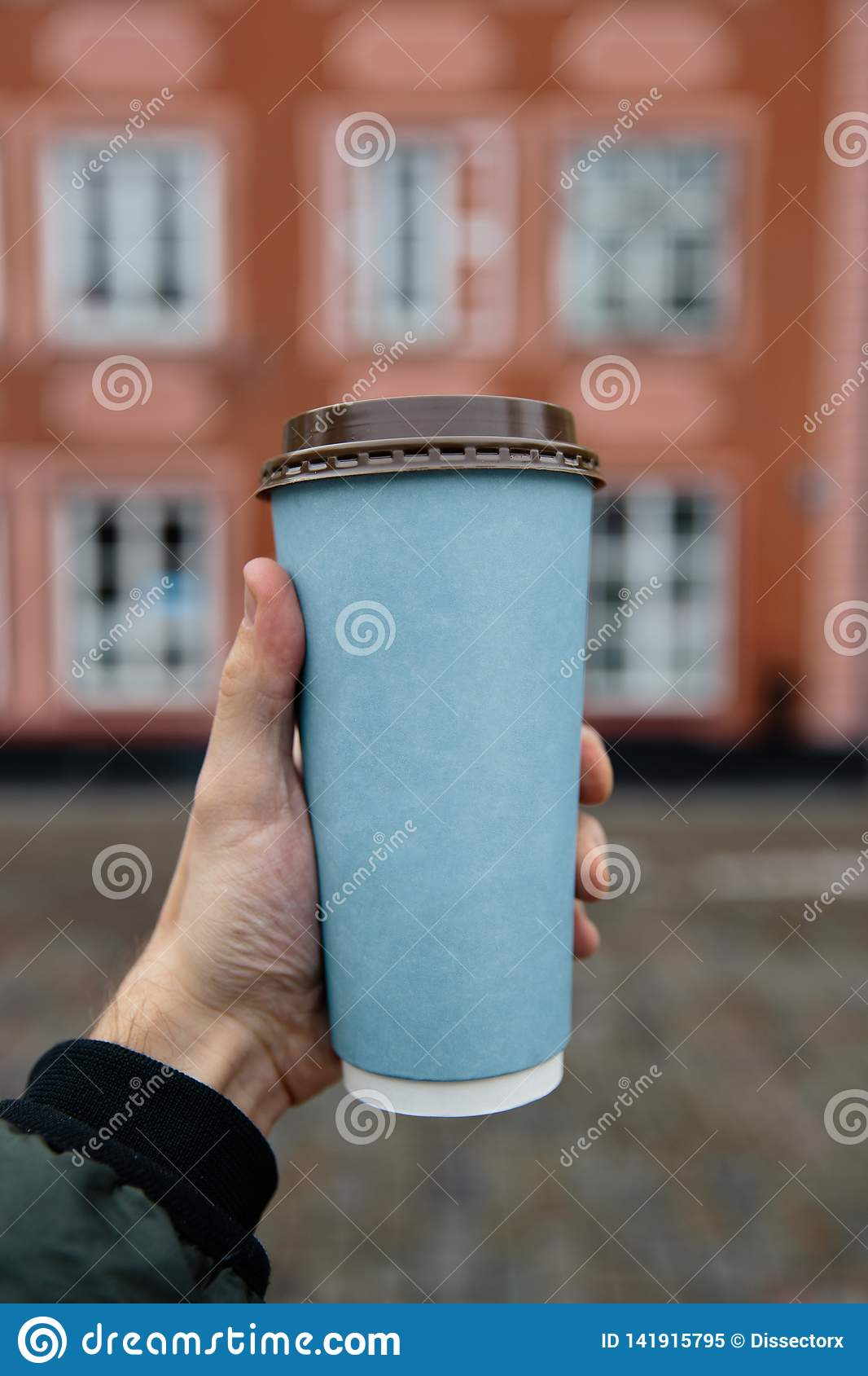 Mockup ad: Male hand holding a blank paper cup in an old town background