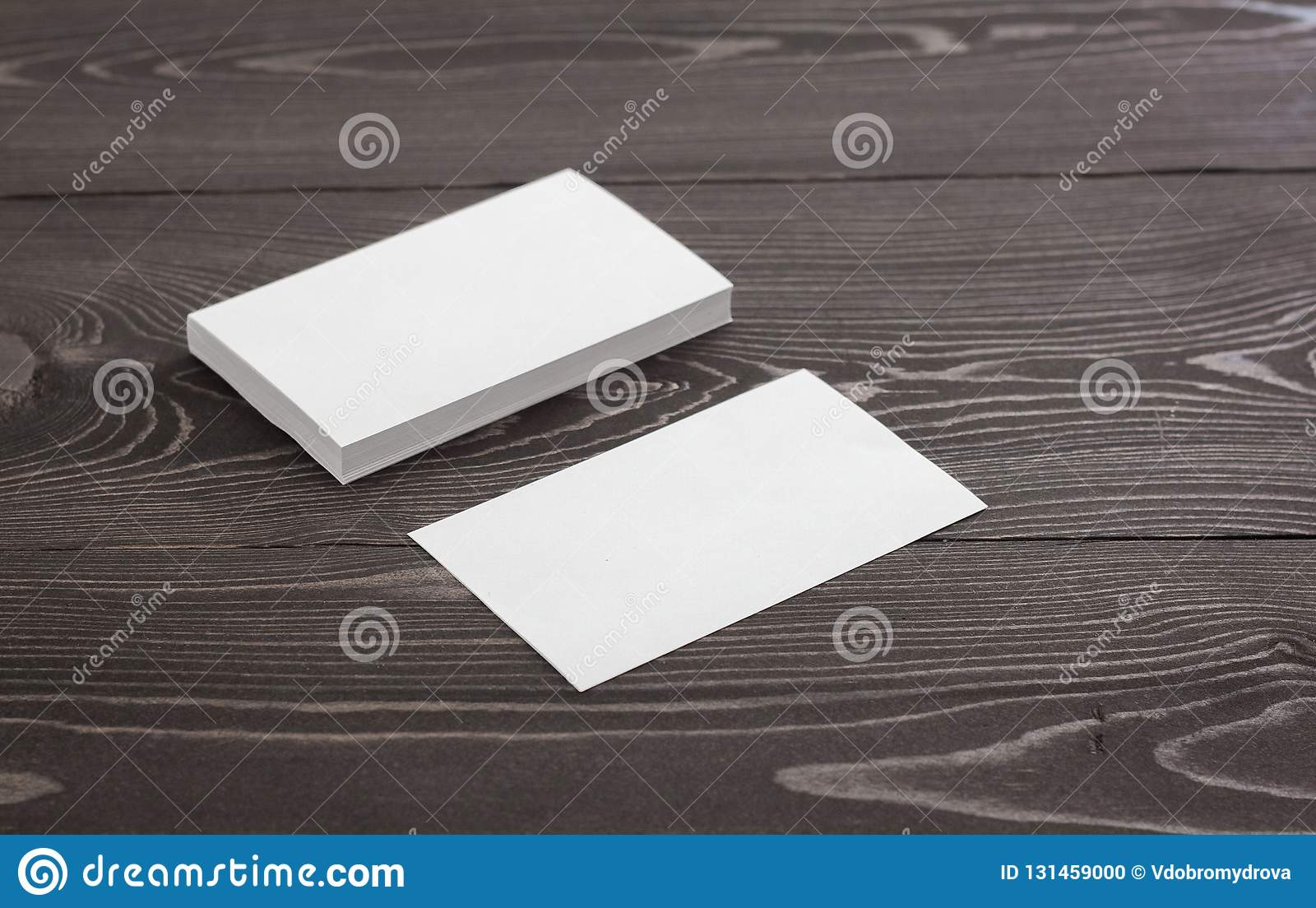 Mockup of business cards on a dark wood background. Template for branding identity