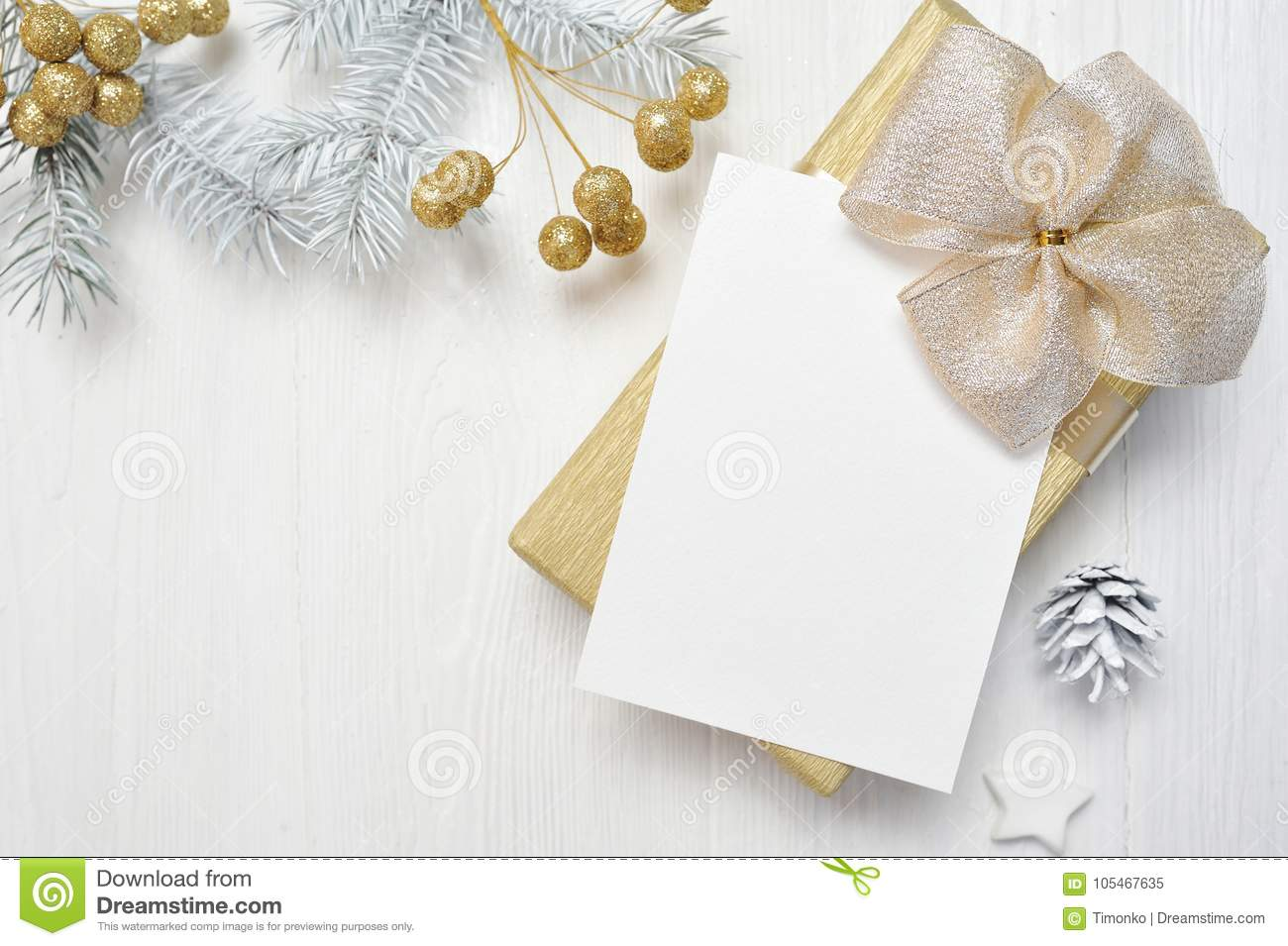 Mockup Christmas gift gold bow and tree cone, flatlay on a white wooden background, with place for your text