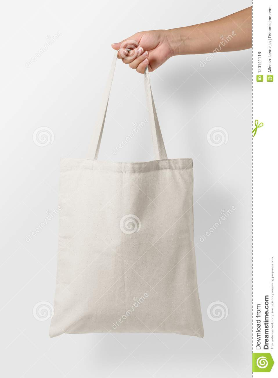 Mockup of female hand holding a blank Tote Canvas Bag on light grey background.