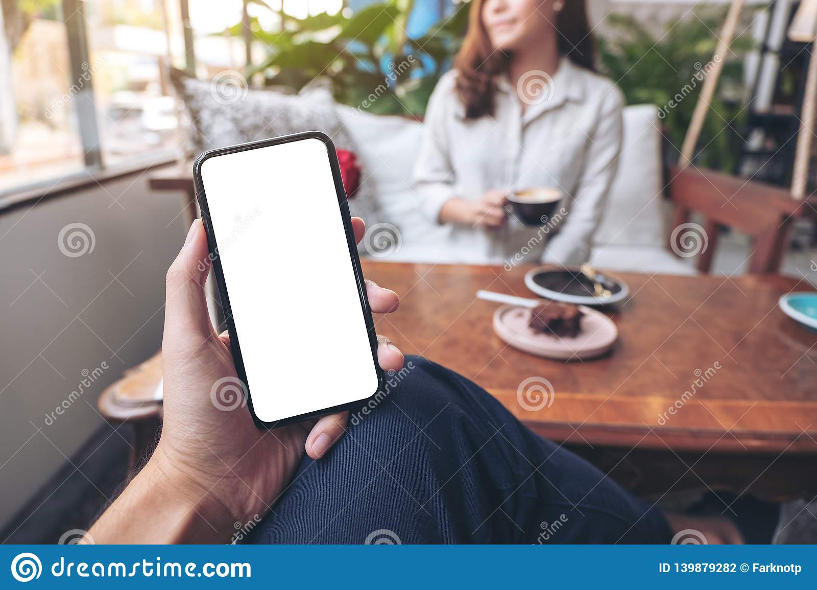 A man`s hand holding black mobile phone with blank white screen with woman sitting in cafe