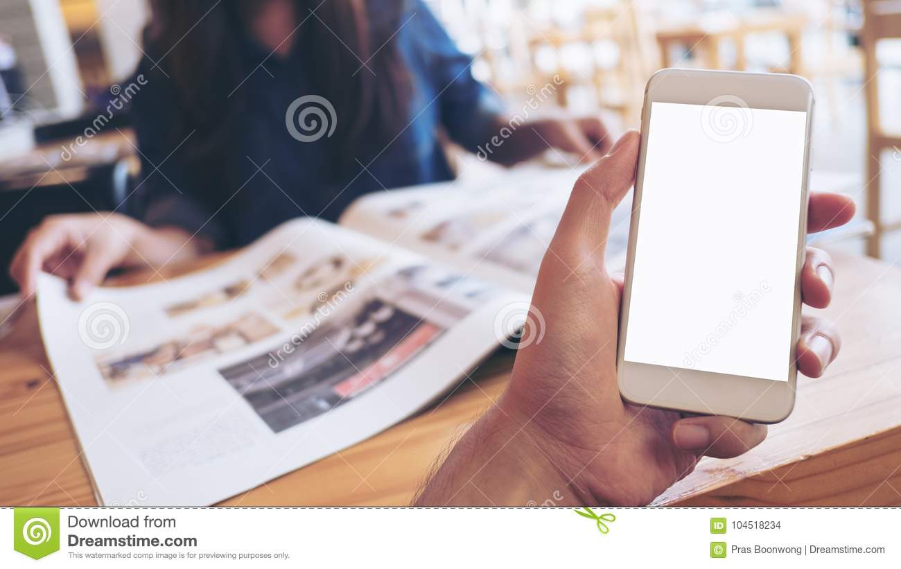 Mockup image of a man`s hand holding white mobile phone with blank screen in modern cafe and blur woman reading newspaper