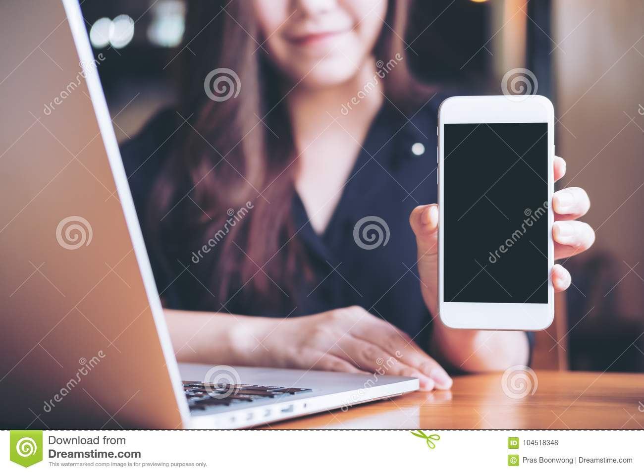 Mockup image of a smiley Asian beautiful woman holding and showing white mobile phone with blank black screen while using laptop
