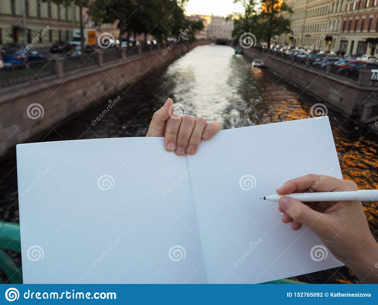 Mockup of person hand holding blank white notebook preparing to write down his or hers ideas.