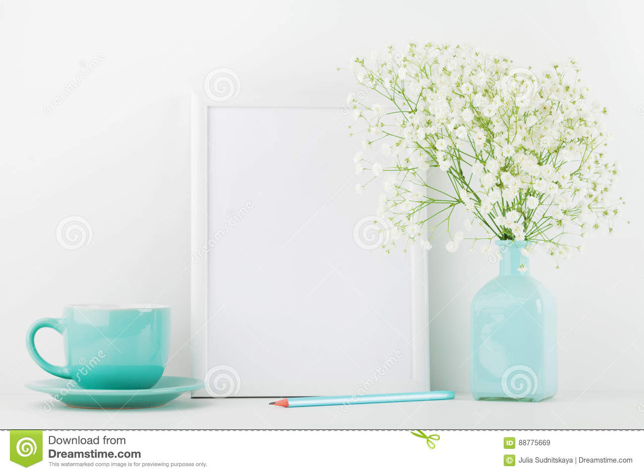 Mockup of picture frame decorated flowers in vase and coffee cup on white table with clean space for text and design your blogging