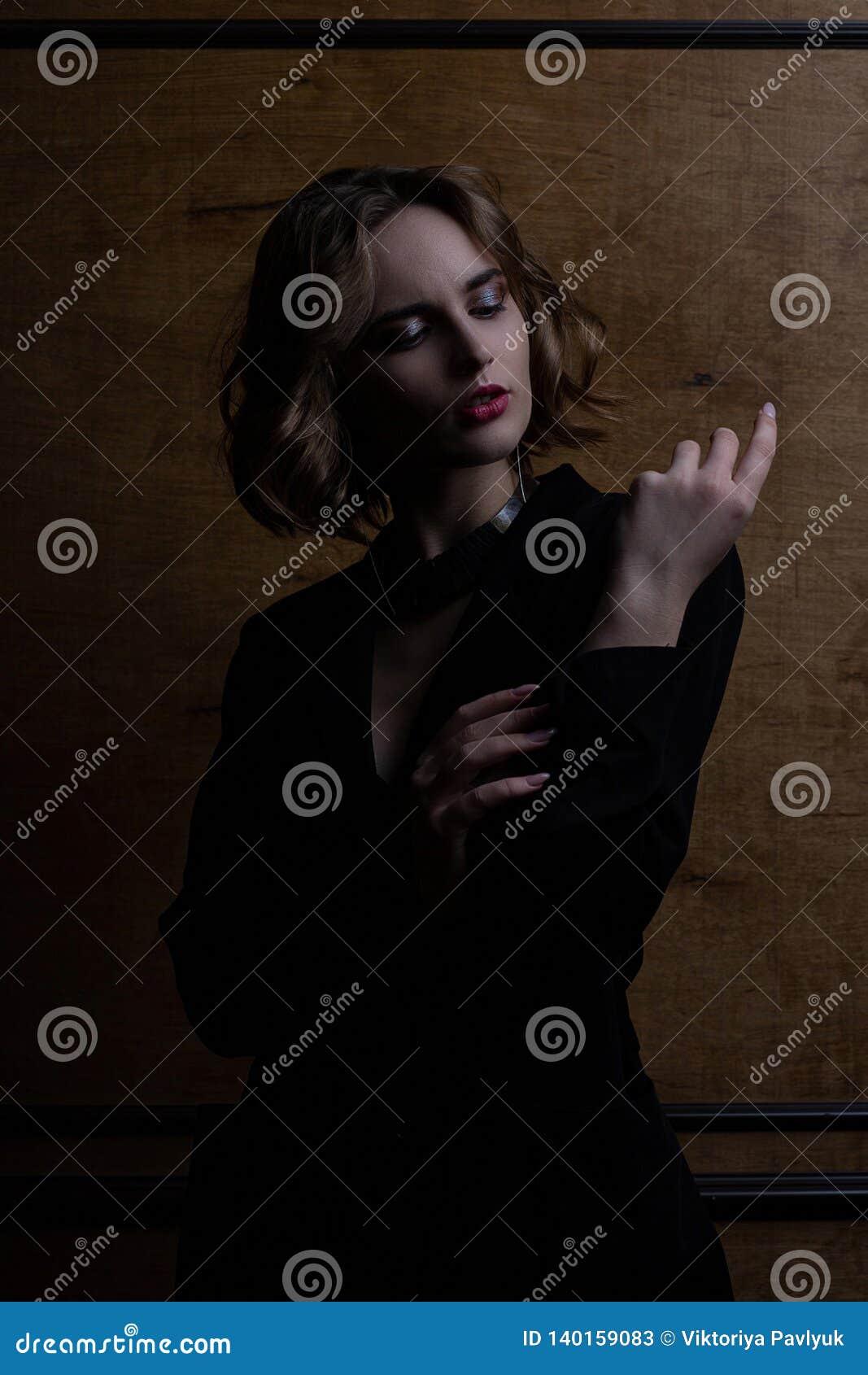 Modèle élégant de brune avec les cheveux bouclés utilisant la veste noire posant avec la lumière de contraste