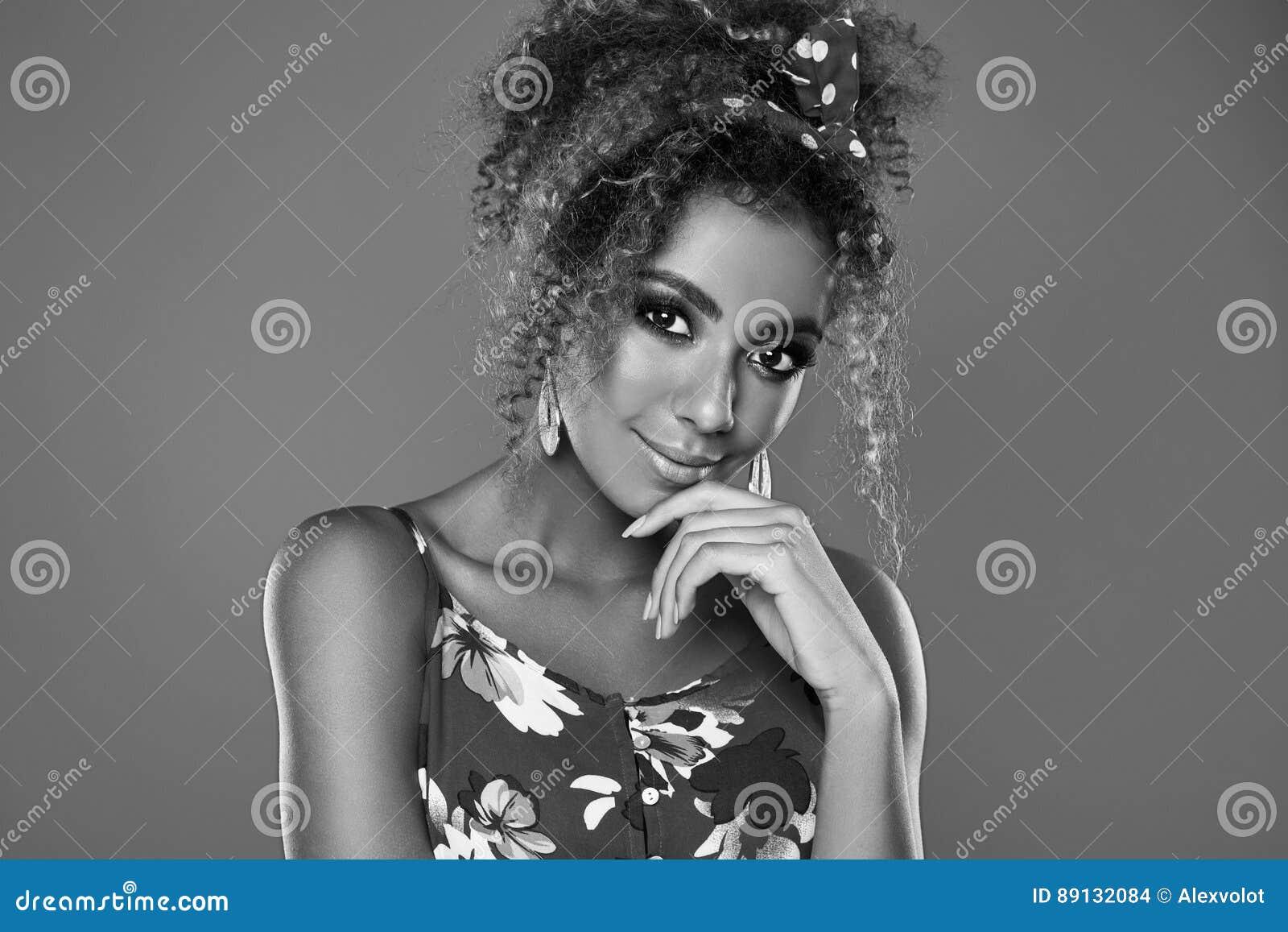 Modèle élégant de femme de couleur avec les cheveux bouclés dans la robe rouge