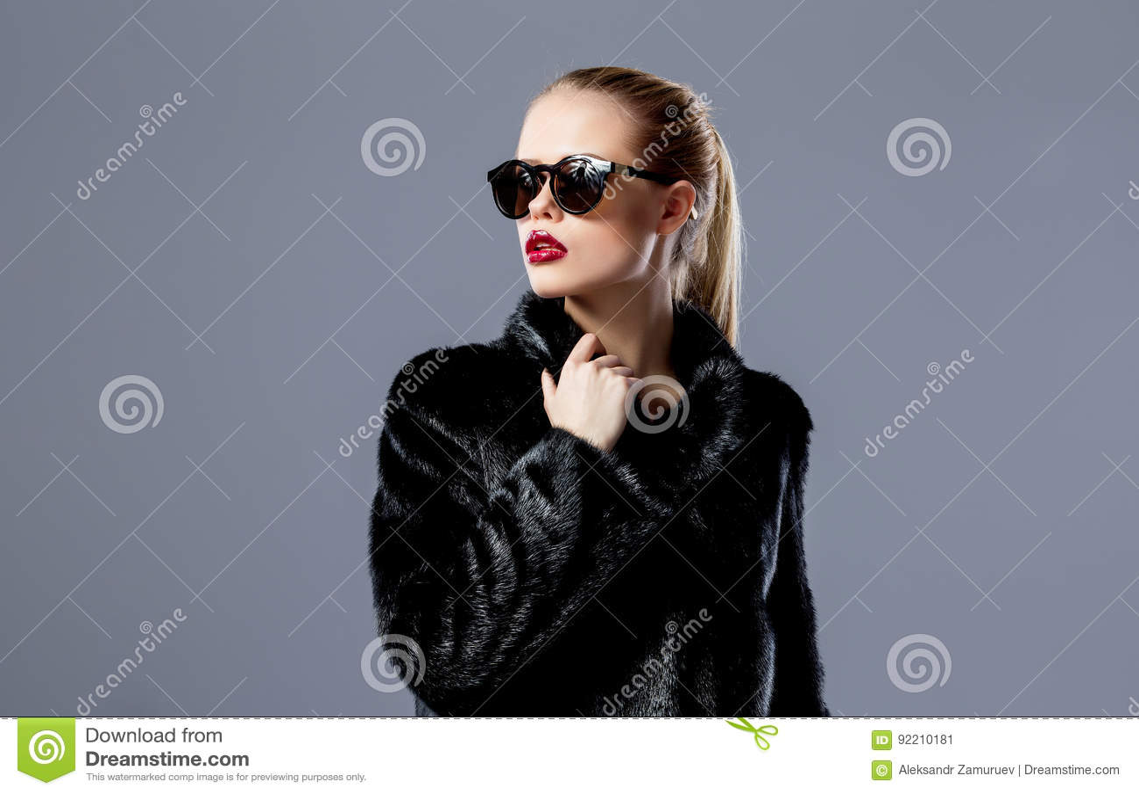 Modèle blond élégant dans les lunettes de soleil et le manteau de fourrure noir