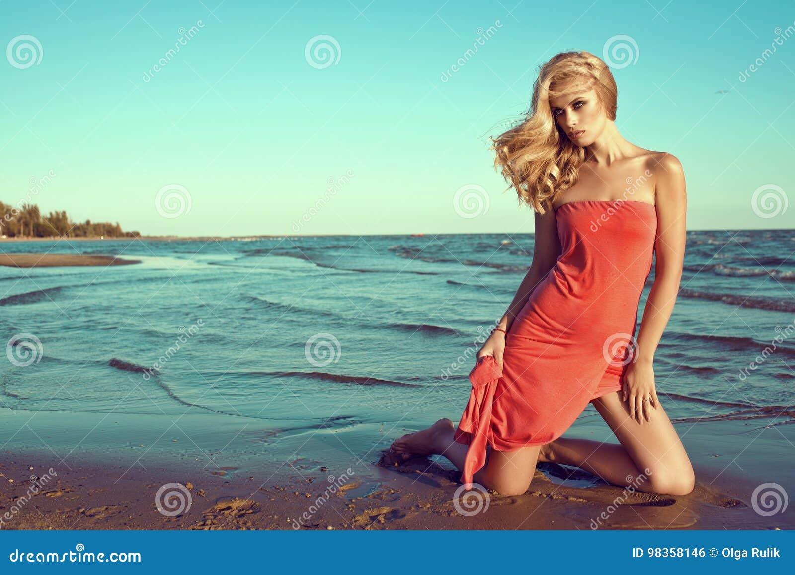 Modèle blond mince sexy magnifique dans la robe sans bretelles rouge de corail se tenant sur des genoux dans l eau de mer et rega