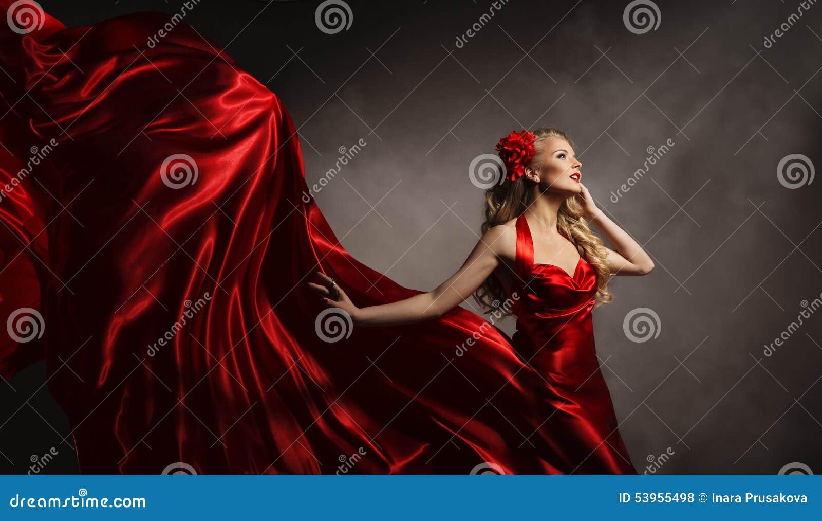 Modèle dans la robe rouge, femme de charme posant le tissu de soie de vol