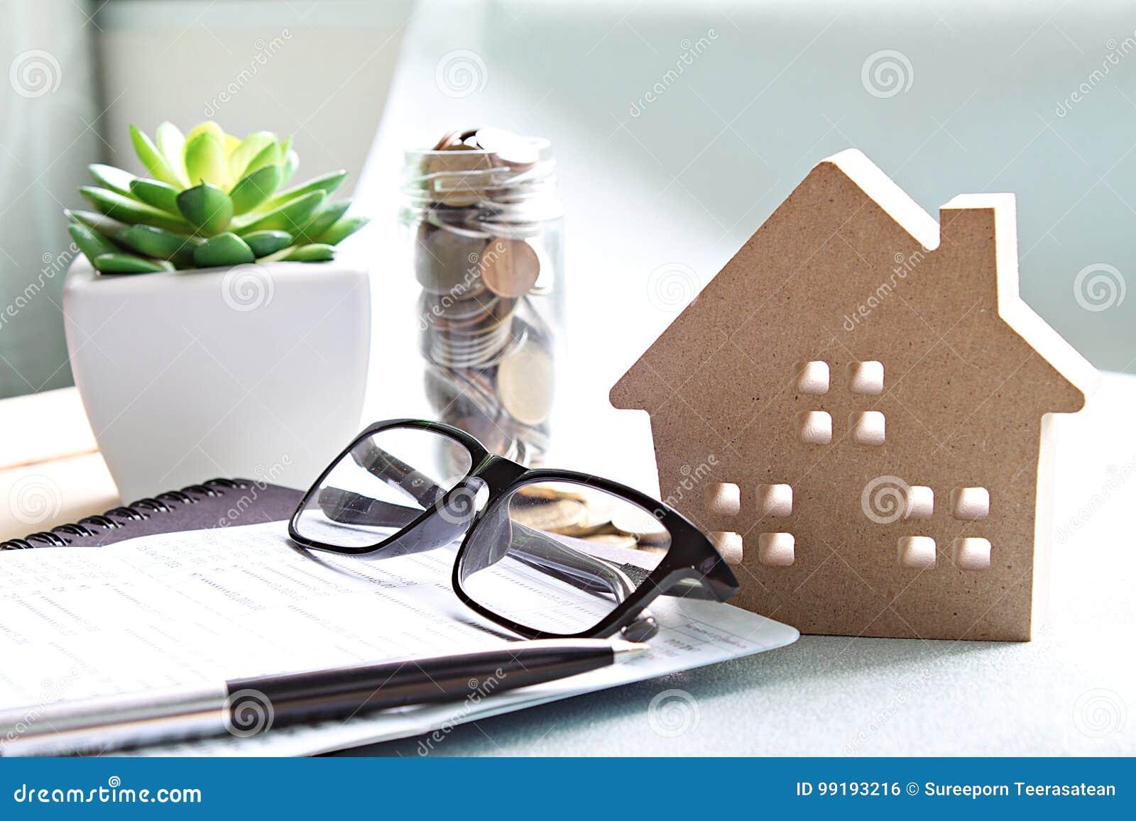 modèle de maison en bois, pièces de monnaie, lunettes et livre de