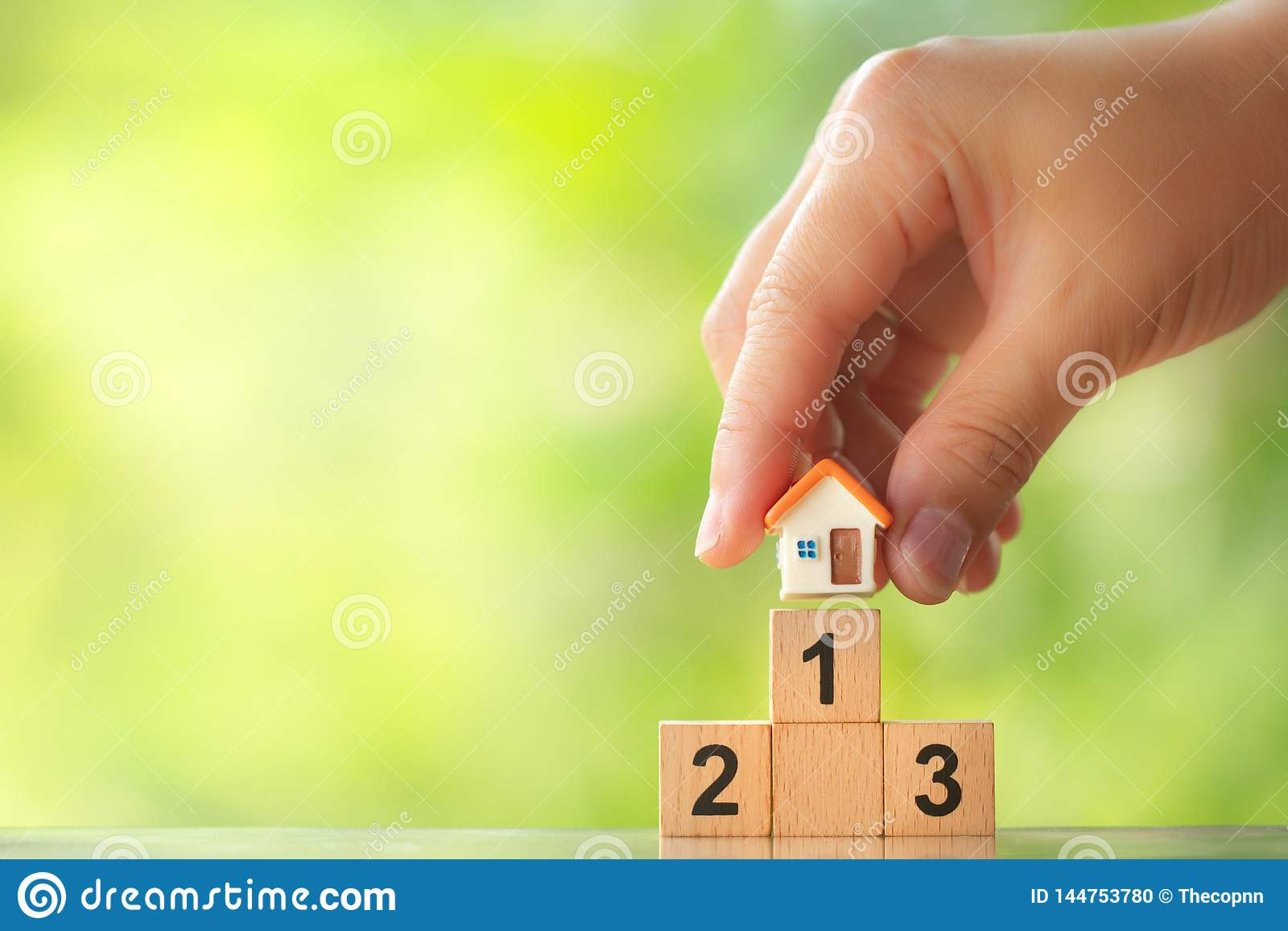 Mod?le de maison de participation de main sur le premier endroit du podium de gagnant sur le fond brouill? par verdure