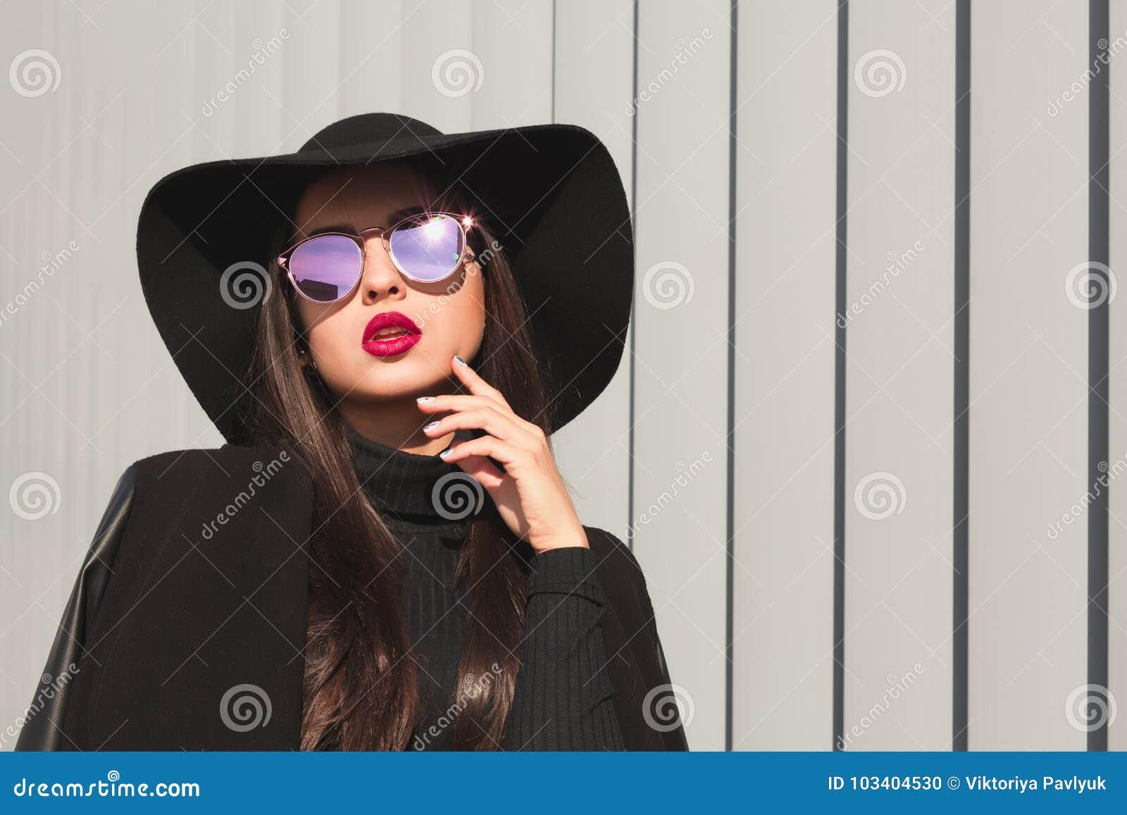 Modèle fascinant de brune dans les verres de miroir et le large chapeau débordé