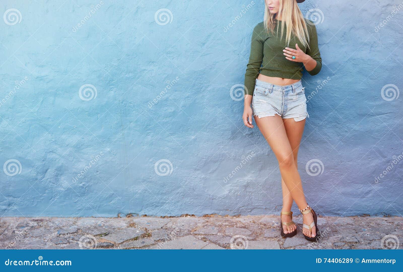 Modèle femelle élégant se tenant contre le mur bleu