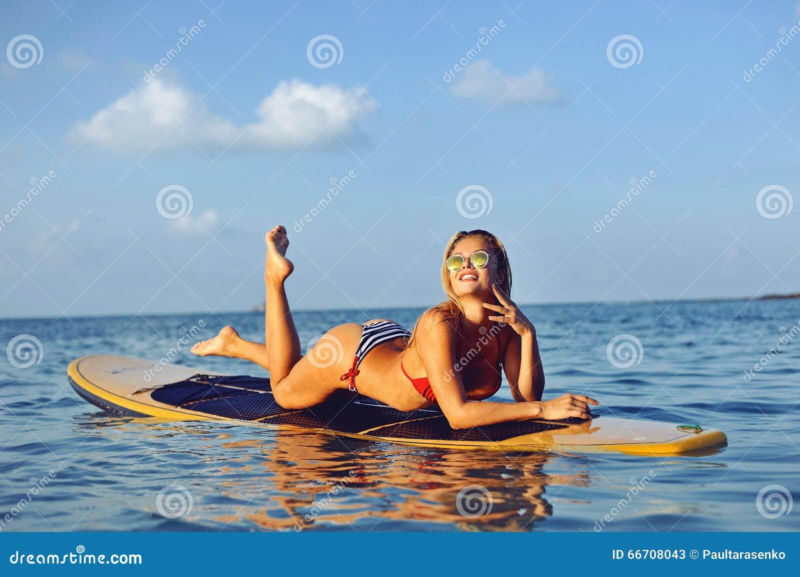 Modèle femelle sexy sur la planche de surf en mer