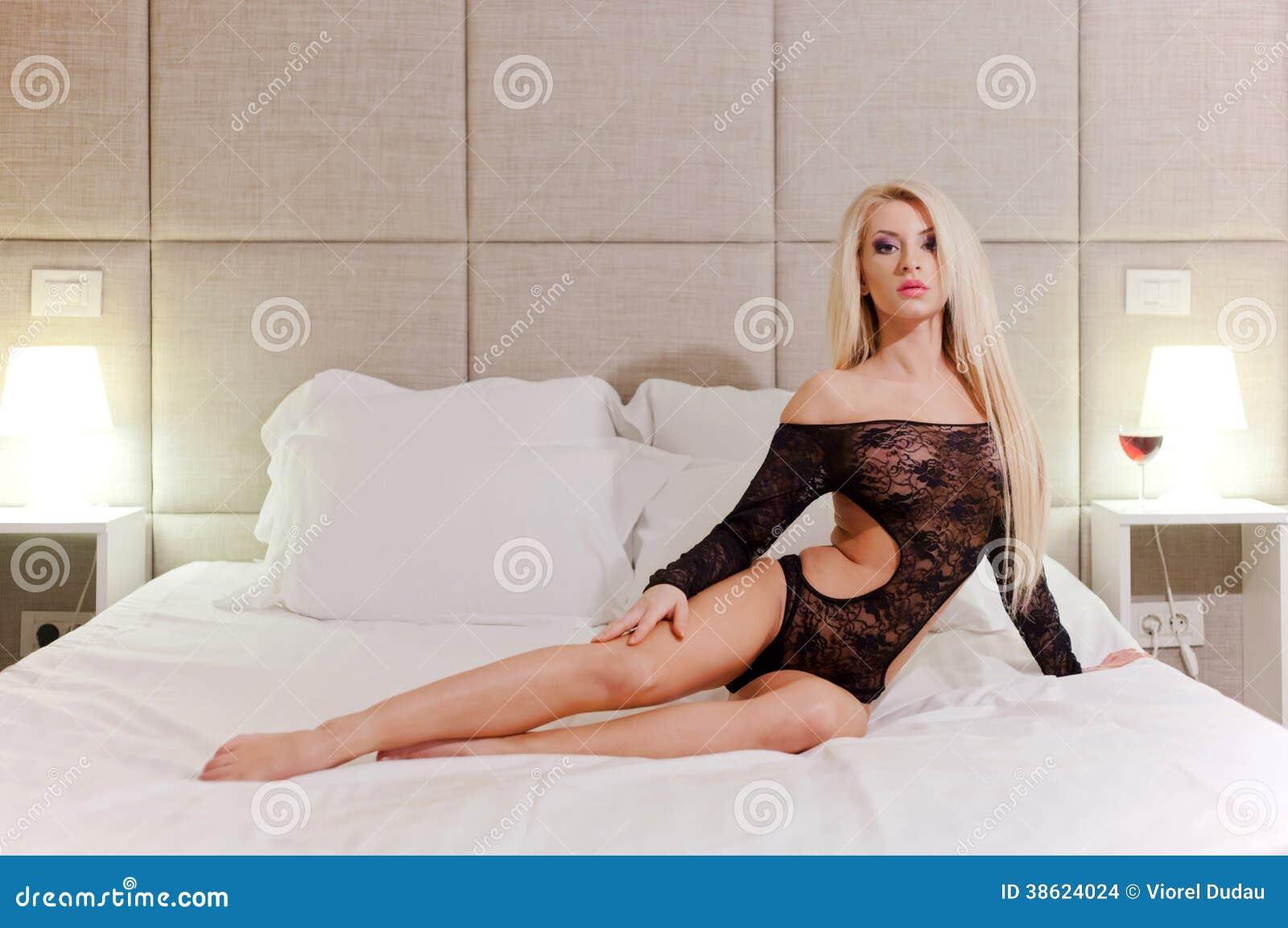 Modèle femelle sur le lit mou blanc
