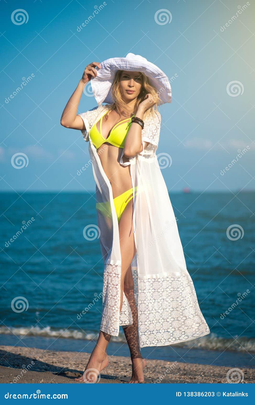Modèle magnifique de fille sur la plage sur le bord de la mer dans le maillot de bain jaune, la robe blanche et le grand chapeau
