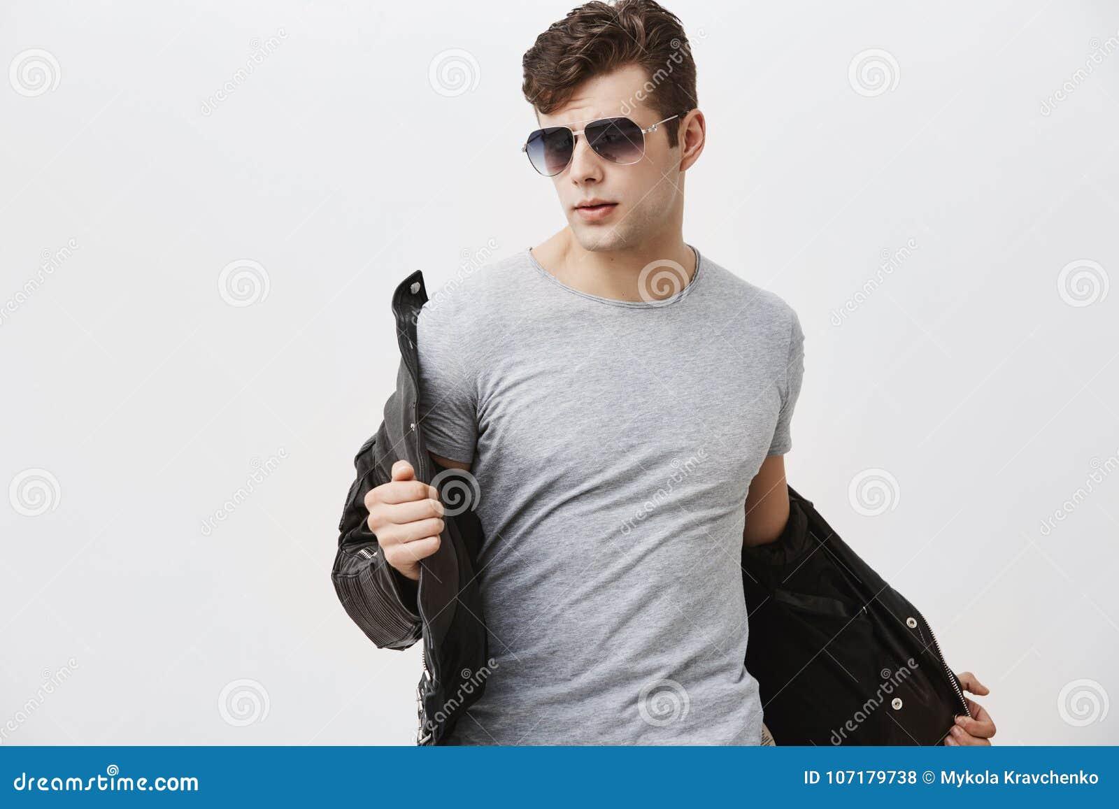 Modèle masculin caucasien avec le sembler d appel posant à l intérieur sur le fond gris Homme attirant bel élégant avec