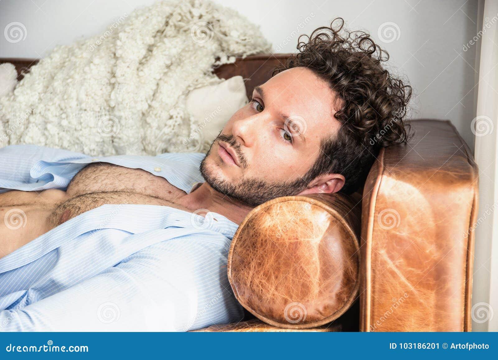 Modèle masculin sexy sans chemise seul se trouvant sur le divan