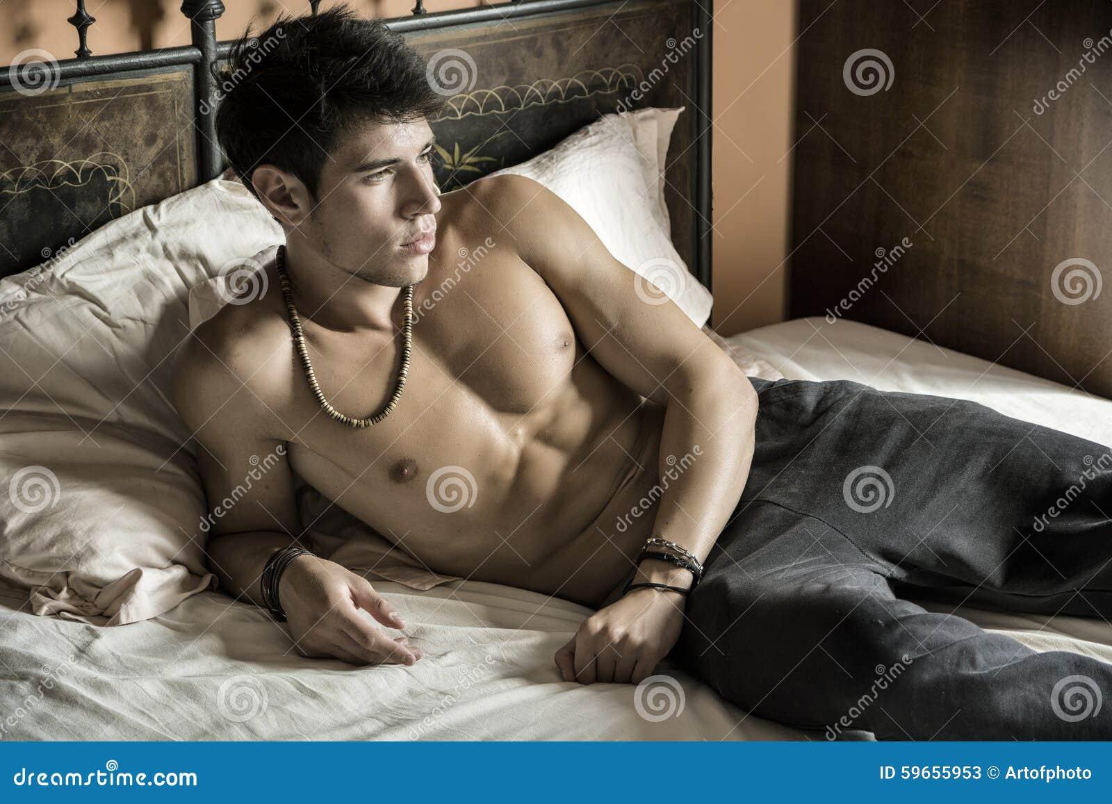 Modèle masculin sexy sans chemise seul se trouvant sur son lit