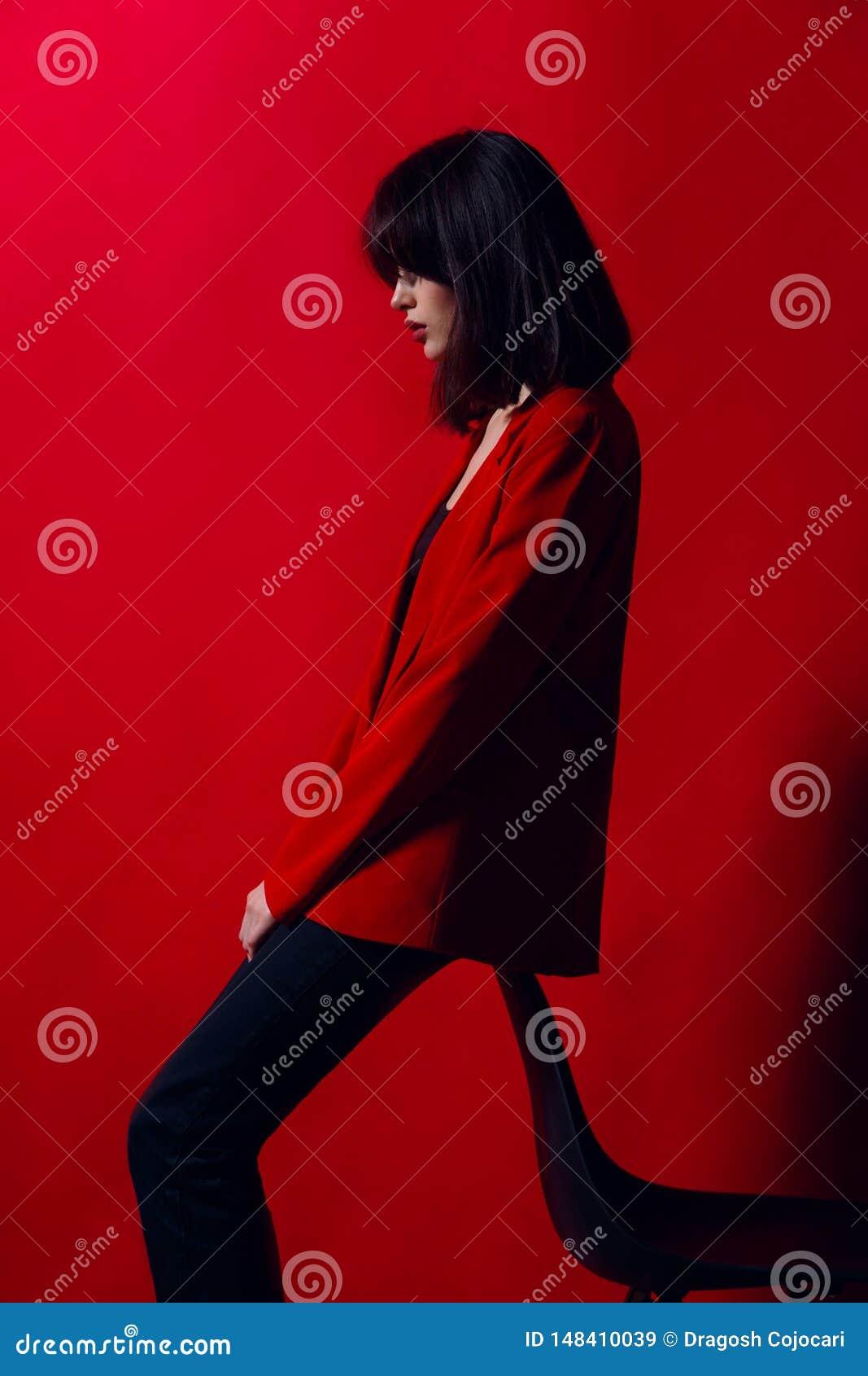 Modèle mince de brune jeune posant dans le costume rouge à la mode et le pantalon noir, près de la chaise, sur un fond rouge