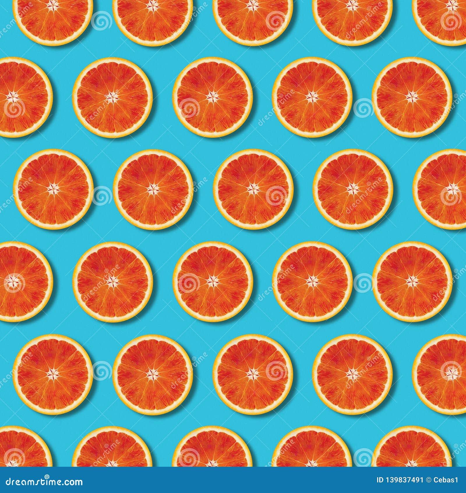 Modèle orange rouge de tranches de vue supérieure sur le fond vibrant de turquoise