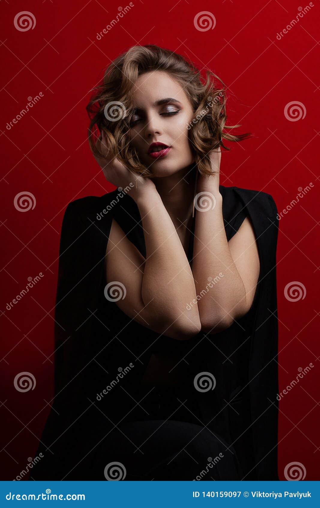 Modèle sensuel de brune avec les cheveux courts onduleux posant avec la lumière de contraste au fond rouge