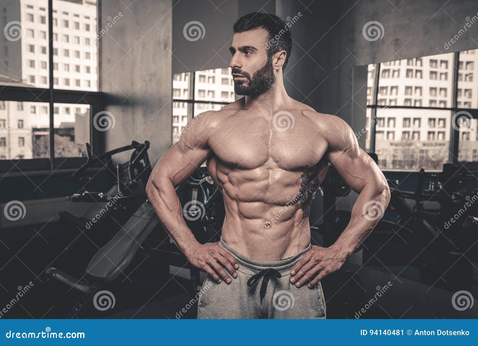 Modèle sexy caucasien de forme physique dans la fin de gymnase vers le haut de l ABS