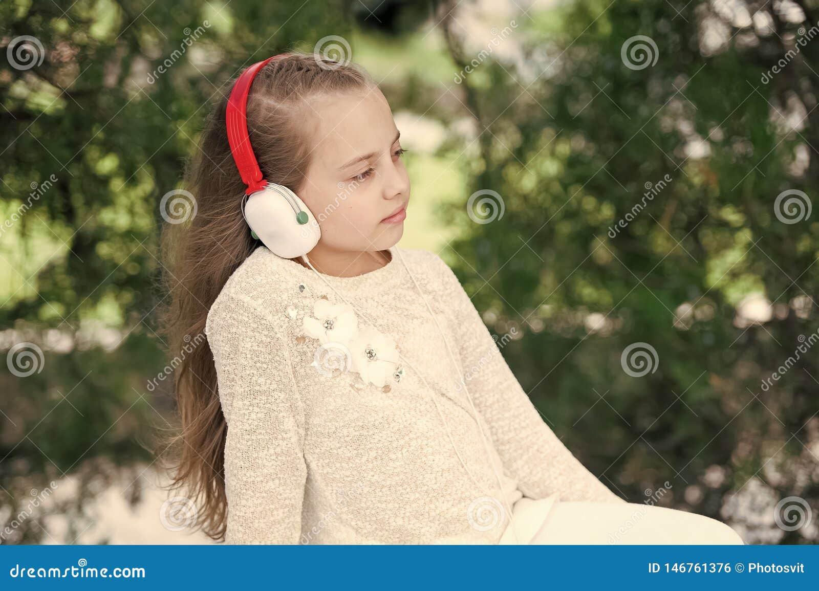 Moda dzieciak i nowo?ytna technologia Melodia d?wi?k i mp3 Ma?a dziewczynka s?ucha muzyk? w lato parku Dziecko cieszy si? muzyk?