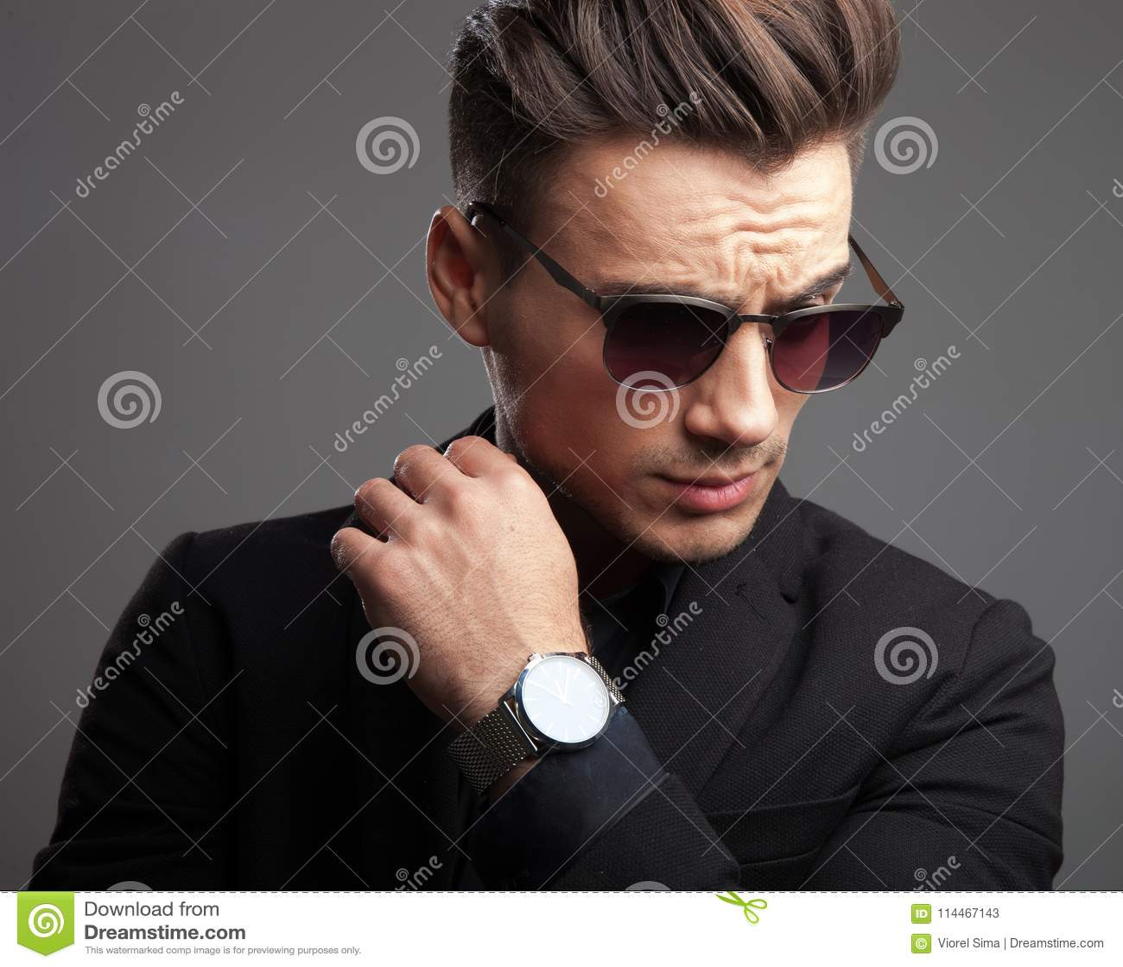 Moda mężczyzna pokazuje jego zegarek i patrzeje w dół strona