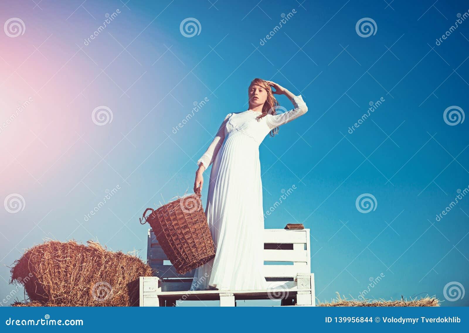 Moda model na niebieskim niebie Albinos dziewczyny chwyta łozinowy kosz z sianem na pogodnym plenerowym pinkinie Kobiety panna mł
