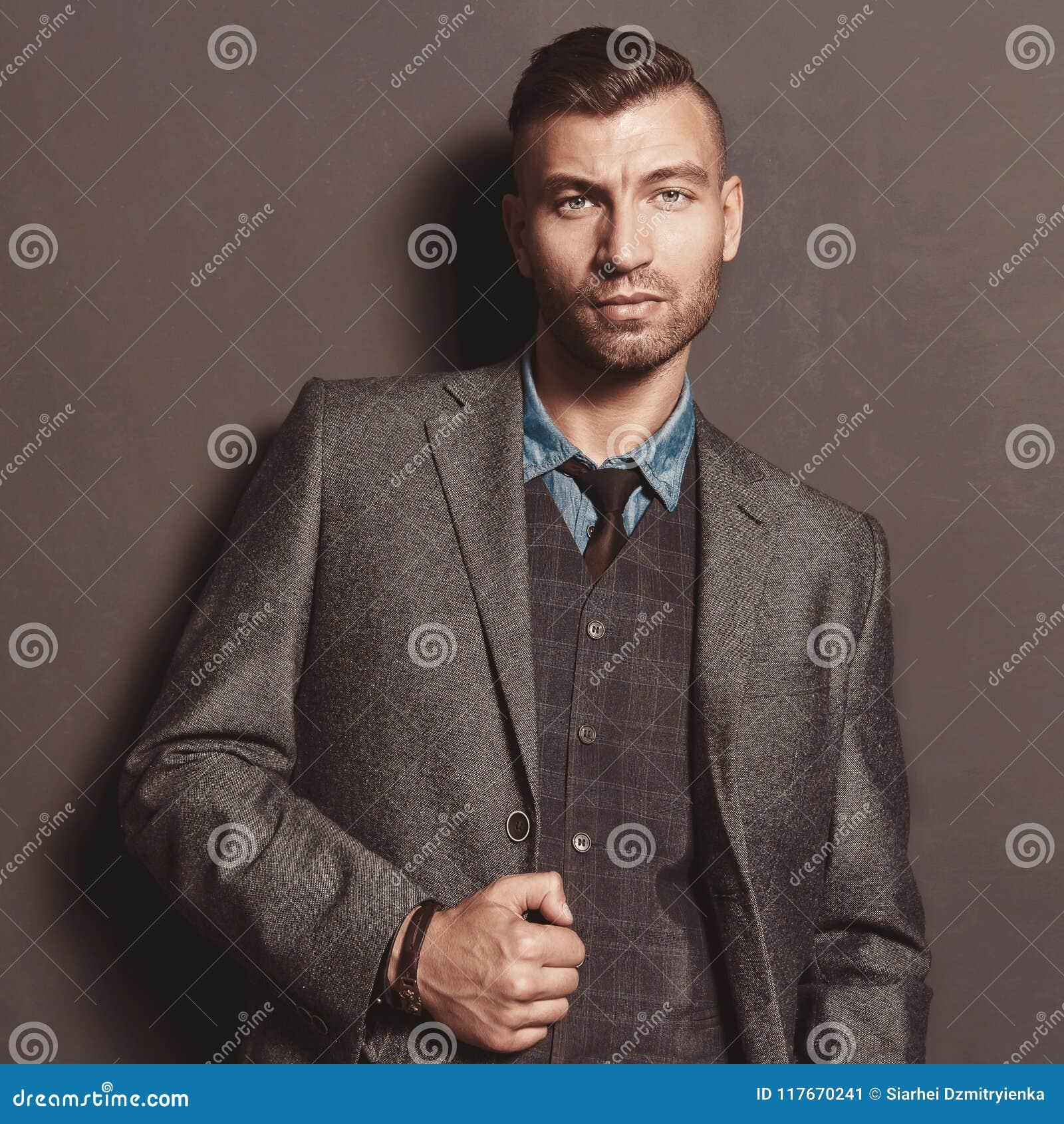 Moda modela przystojny elegancki mężczyzna w kostiumu na szarość izoluje tło Elegancki modny piękny brutalny mężczyzna