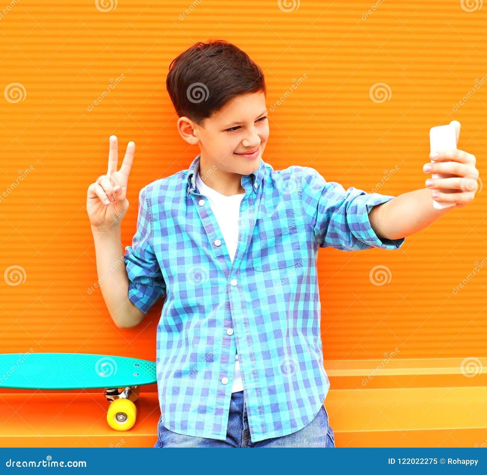 Moda nastolatka chłodno chłopiec bierze obrazek jaźni portret