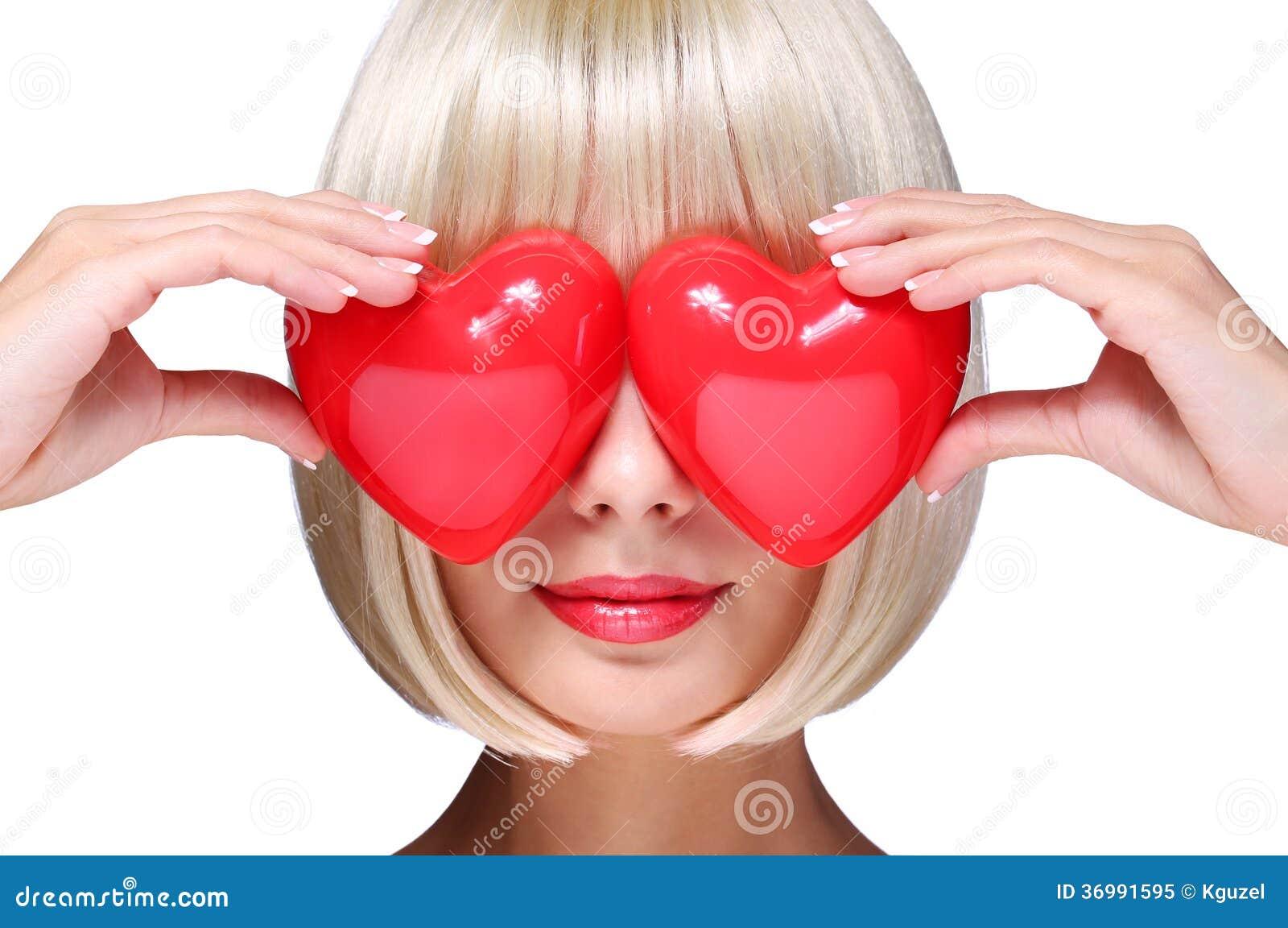 Mode-blondes Mädchen mit roten Herzen am Valentinsgruß-Tag. Bezaubernd