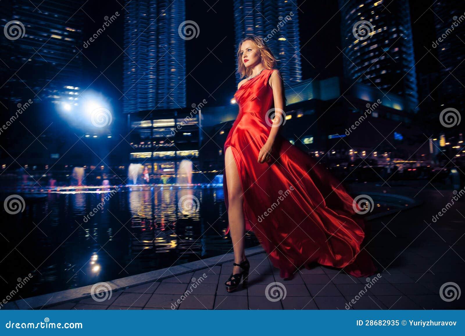 Mode-Dame In Red Dress und Stadt-Leuchten