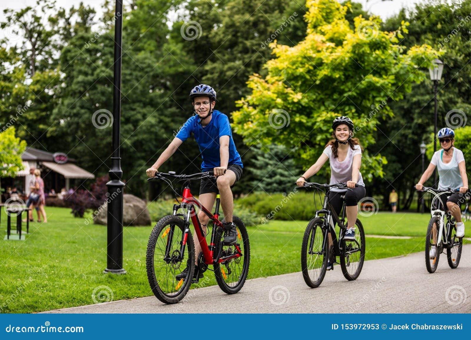 Mode de vie sain - bicyclettes de monte de personnes en parc de ville