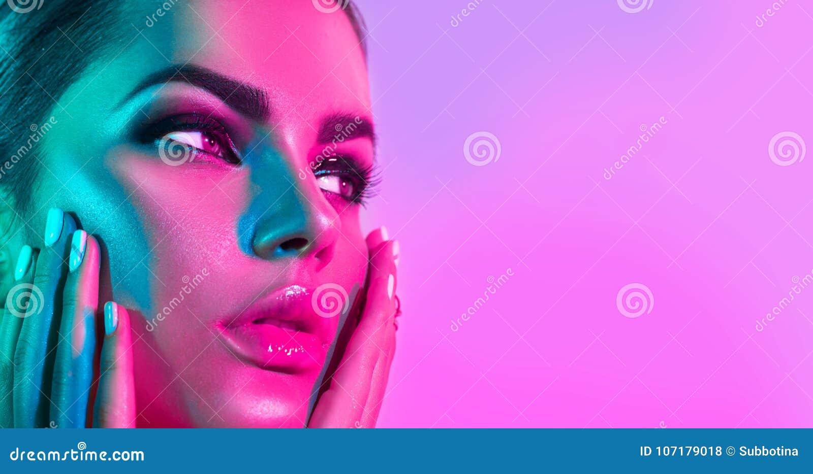 Mode-Modell-Frau in den bunten hellen Lichtern mit modischem Make-up und Maniküre