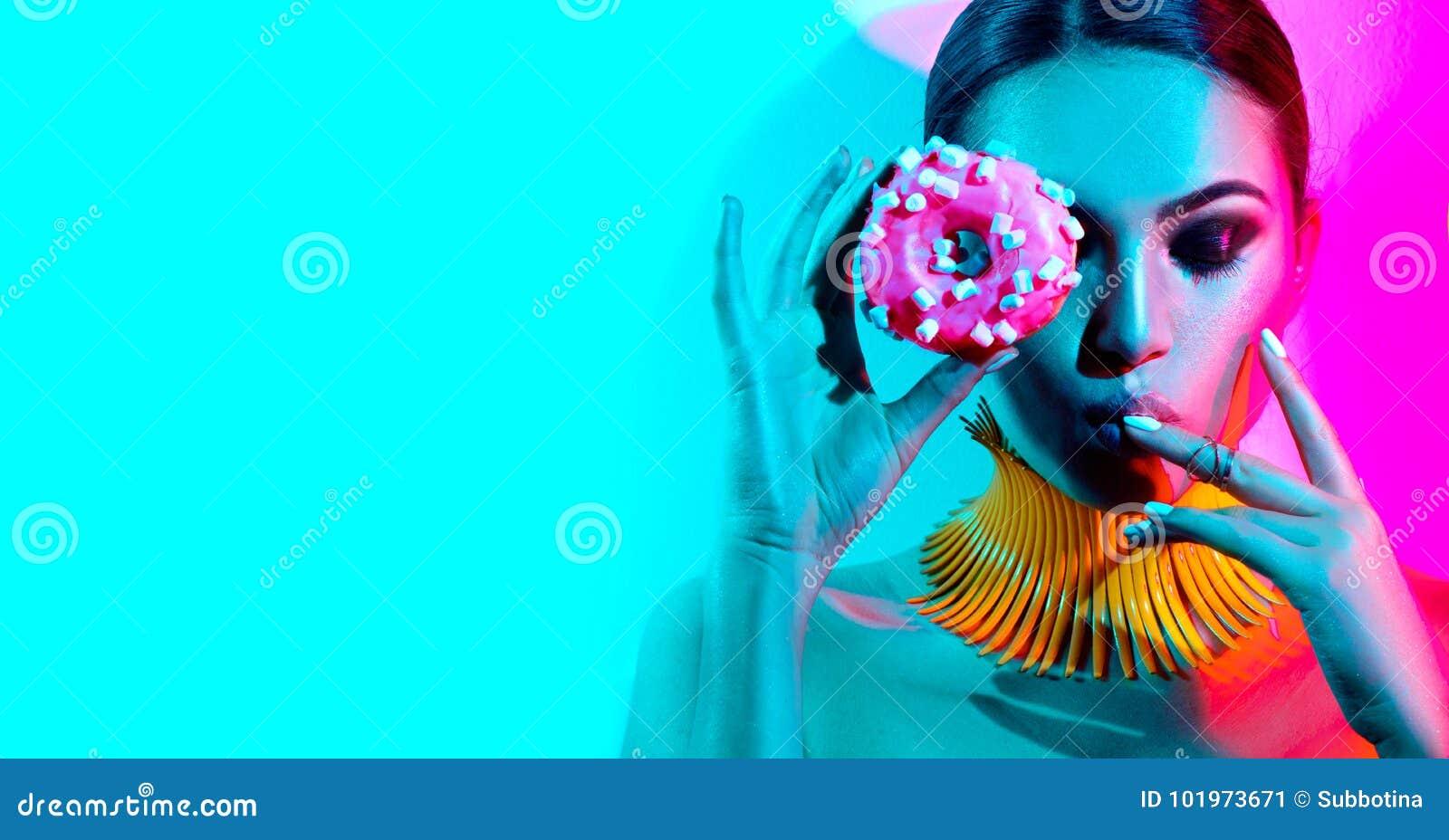 Mode-Modell-Frau, die im Studio mit Donut aufwirft
